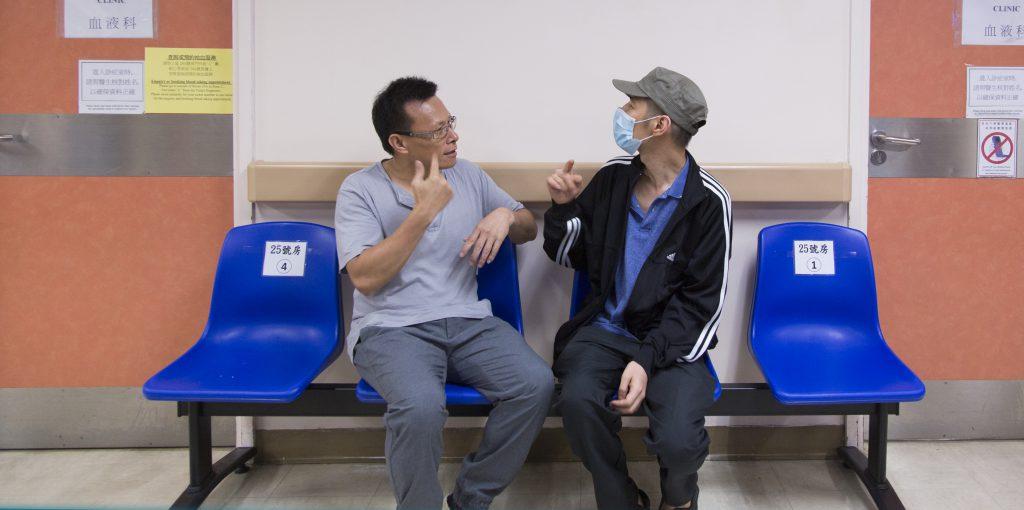 手語翻譯員邵日贊(左)陪伴聾人黃念忠(阿忠)到醫院覆診。