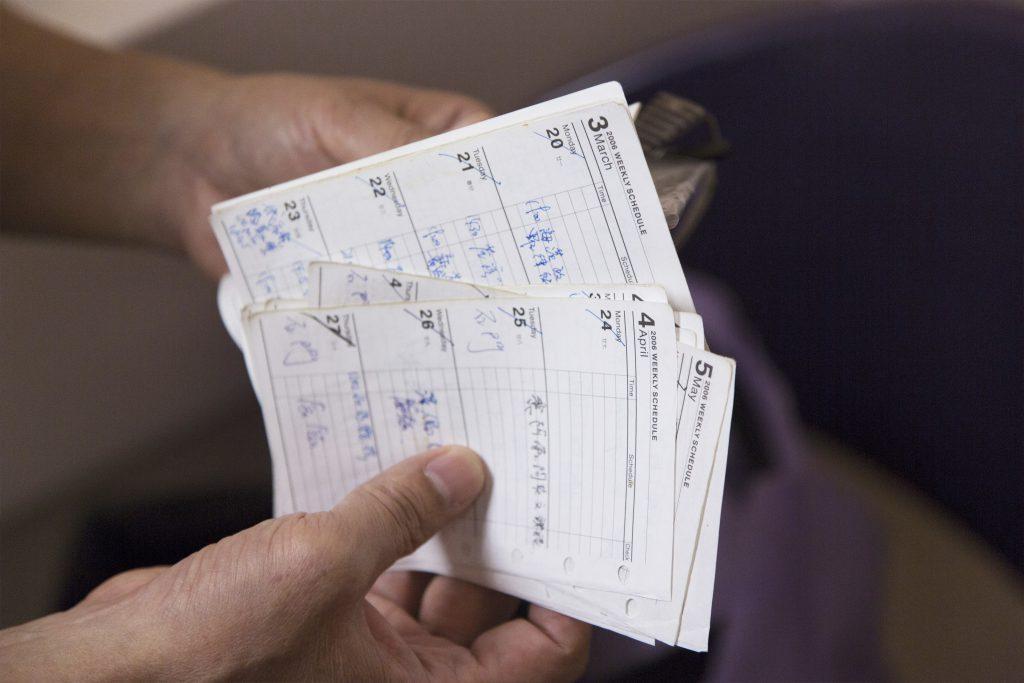 邵日贊翻閱過往的記事簿,幾乎每天也要協助聾人作手語翻譯。