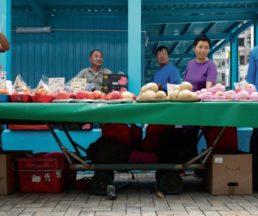 六十歲的伍順文(左二),把賣生果的小販車推到粉嶺聯和墟的一段行人路彎角處,「這為角位不阻人。」
