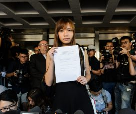 Pro-independence lawmaker Yau Wai-ching (C) holds a court ruling as she leaves the High Court in Hong Kong on November 15, 2016. A Hong Kong court on November 15 ruled to disqualify two pro-independence lawmakers from parliament, a week after Beijing said it would not allow the pair to be sworn into office as fears grow of the city's liberties coming under threat. / AFP PHOTO / ANTHONY WALLACE
