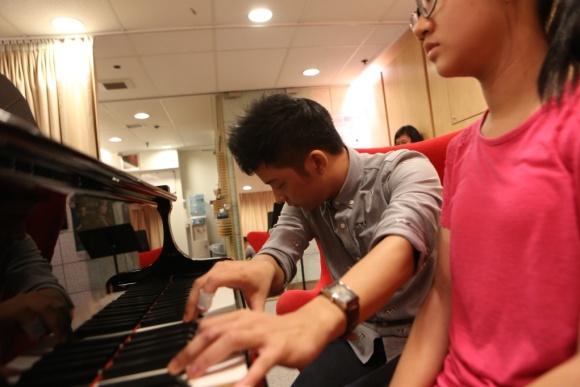 聽見不對勁,焦急着緊上來,黃家正便俯身摸上琴鍵,演示他理解中的樂曲模樣。