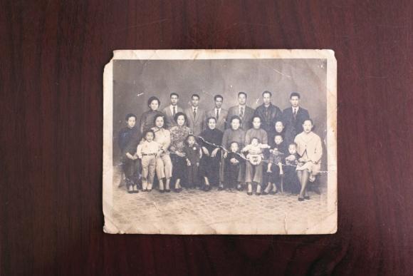 舊照中,坐在前排左二是七姑母,左三是五姑母,梁紀昌一 家站在照片的最右邊,抱着球的小孩便是他。