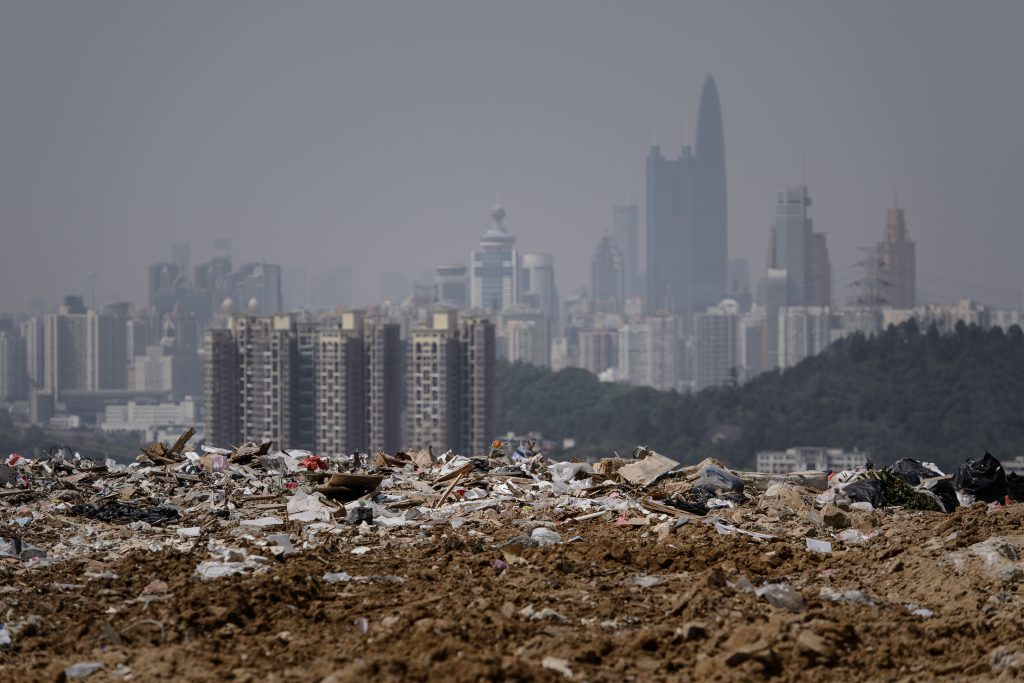TO GO WITH: Lifestyle-Hong Kong-Environment-Waste by Laura Mannering This picture taken on March 6, 2013 shows a landfill in the new territories of Hong Kong as the Chinese city of Shenzhen looms in the background. Official data shows that the city generates about 19,000 tonnes of solid waste every day, with 9,100 tonnes dumped into landfills -- two thirds of it domestic waste. Only 52 percent of total waste is recycled in a city that produces an average of 921 kilograms of rubbish per person per year, which is more than twice the amount compared to Japan (410kg) and South Korea (380kg), according to the Organisation for Economic Cooperation and Development. AFP PHOTO / Philippe Lopez / AFP PHOTO / PHILIPPE LOPEZ