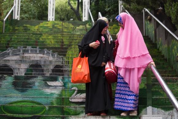 Fatimah(右)穿一襲粉紅衣裙,和她的兩位幫手相視而笑