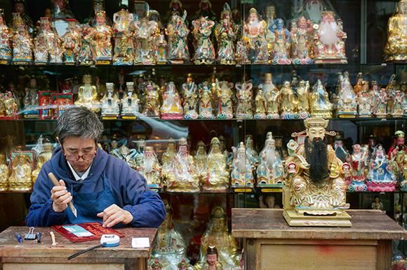 在七十年代開業的郭記木器雕刻,店內神像佛像近1,000個,以文武財神最受顧客歡迎。圖為老闆郭一天。