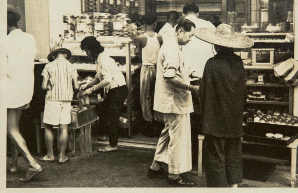 這是香香麵包的前身「香香餅家」,站在店門前衣袖束起的正是年輕時的姜勝和。(圖片由受訪者提供)
