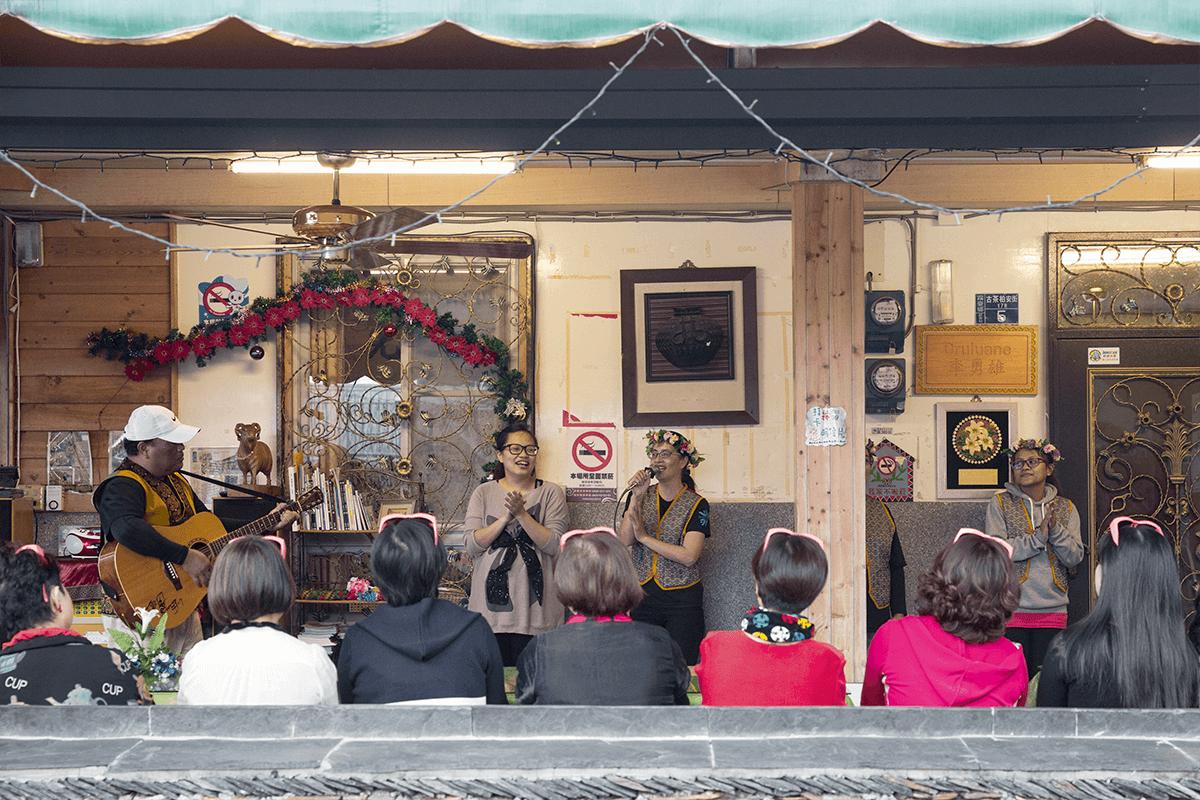 族人給遊客介紹好茶的故事,彈唱民族歌曲。