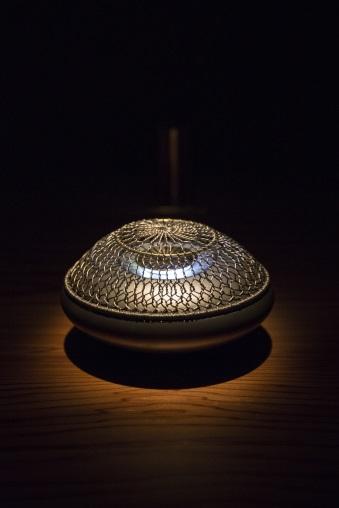 鈦金屬製電香薰爐「網香爐」,靈感來自石頭的形狀,由於鈦屬低導熱性金屬,不怕金屬表面燙傷皮膚。