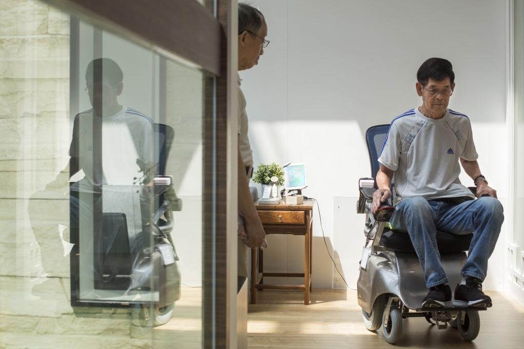 參觀者陳生試坐天行健電動輪椅,自言很易操控。此輪椅設計者胡競樂當初因為發現,輪椅用家經常因為公司缺乏空間讓輪椅移動,而無法就業,故想出這款猶如一般座椅的輪椅。
