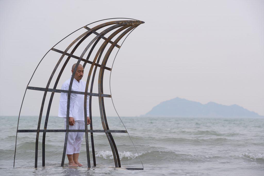 何兆基的作品《告解室》,以鯊魚鰭的造型為參照,是一個彷如囚牢的金屬雕塑結構,雕塑置於海面,人立於其中, 易地而處,反思自身對其他物種之遺害。