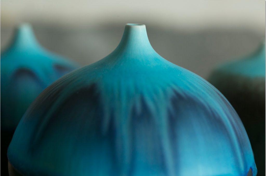 小口花瓶呈現褪色的漸層粉藍,同時擁有強烈的顏色對比。