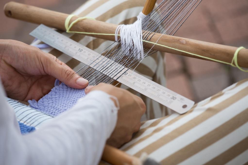 阿健以「背帶織機」示範最古老的手織布方法,另一端繫在柱子上,隨街編織。