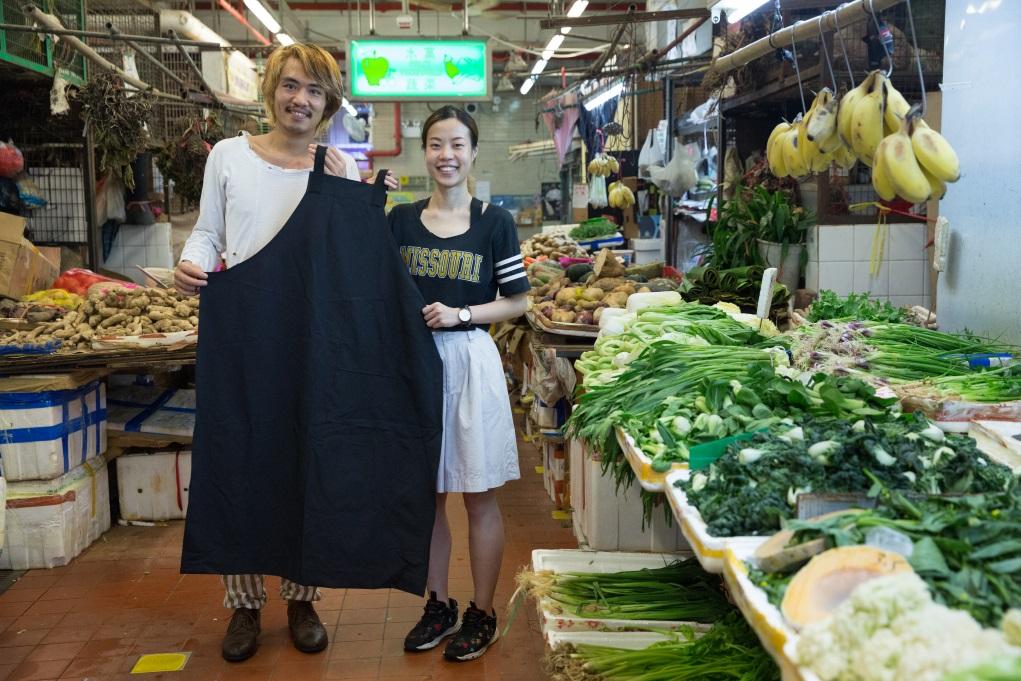 時裝設計師阿健(左)與琳琳花了三個月,了解香車街街市的檔主不同需要,這條圍裙為豆品店而設,長度及腳踝,以免工作時沾濕身體。