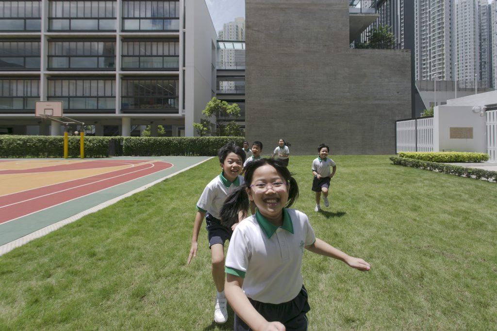 聖公會聖十架小學學生在校園草地上自由奔跑,啟德新校舍在一樓、二樓及天台各設花園。