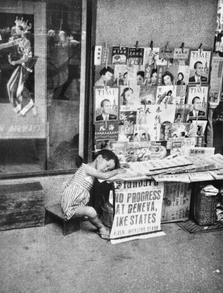 羅蘭士嘉道理工作的中環聖佐治行樓下的報紙檔,小女孩伏在報刊上睡覺。