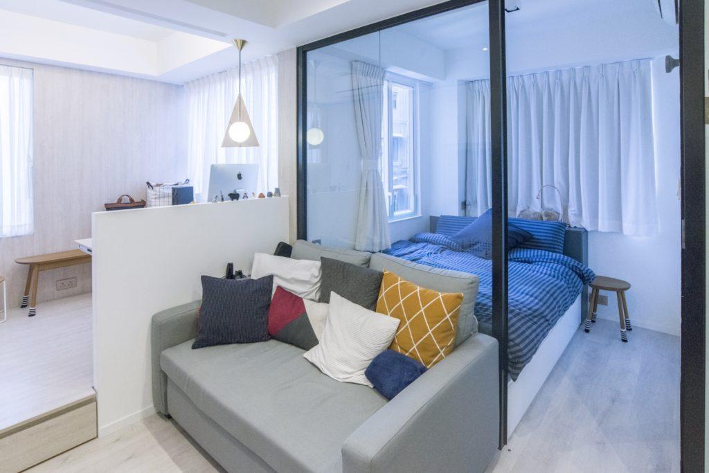 靠窗的位置本來是兩間獨立的房間,白白浪費了自然光;設計師把牆折掉, 改為半開放式的工作間、客廳和睡房,令工作、休息和睡眠的地方都更舒適自在。工作室建於地台之上,以增加儲物空間。