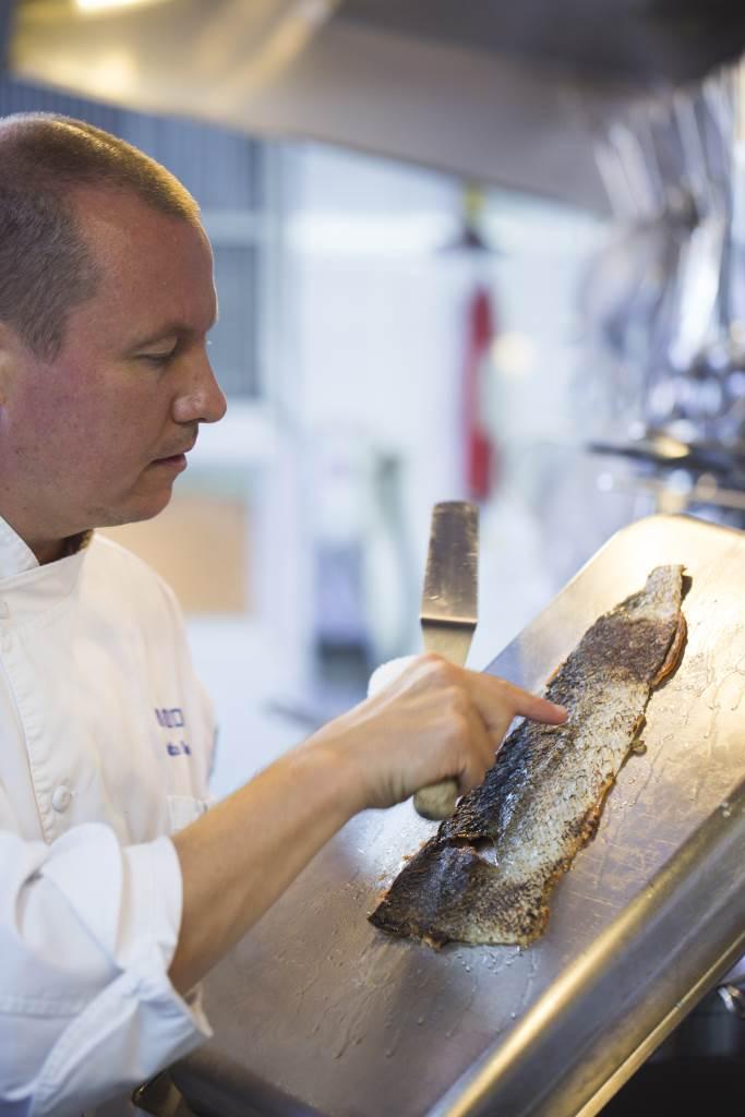 Chef Jaakko小心翼翼的把烘脆了的三文魚皮剔出來。