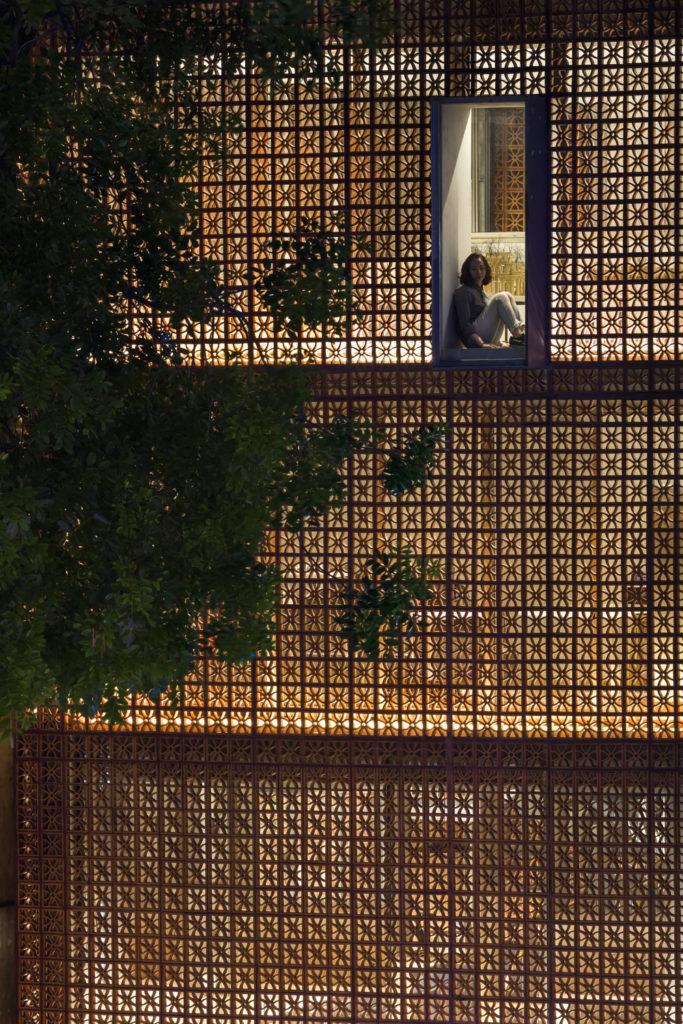 Vo Trong Nghia就巧妙利用鑲空赤土磚,讓室內的燈光可以透出,襯托出大樹的形狀。