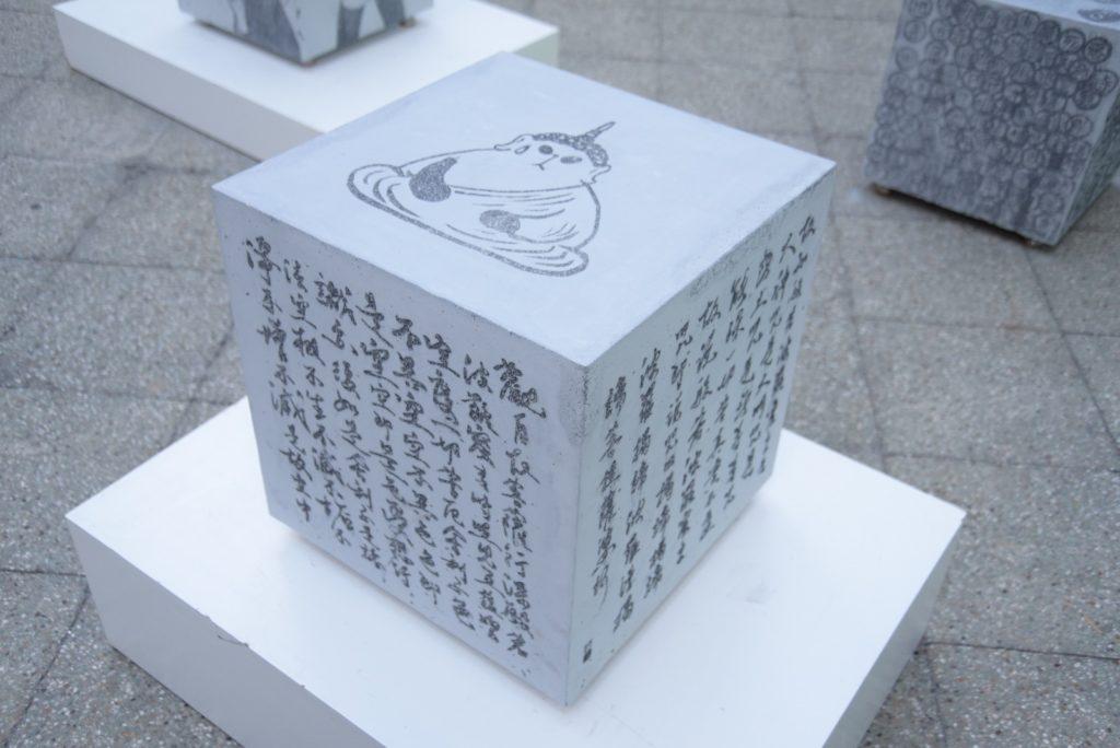 《心經》 「水泥立方凳」的創作人包括Graphic Airlines、門小雷、Paul Lung等,其中小克的作品刻印了心經及聾貓化身的佛祖。