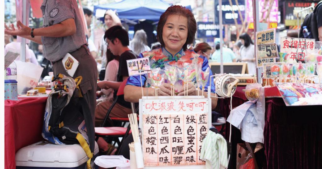 人稱「糖姨」的鍾婆婆十分留意墟市的檔期,四處擺檔,宣傳吹波糖手藝。