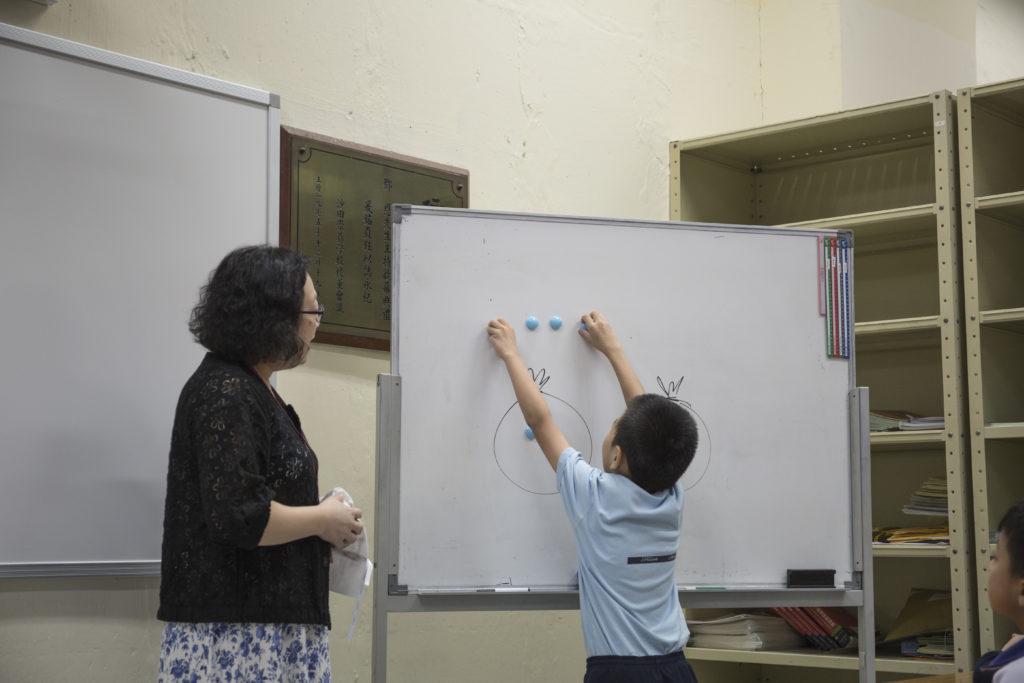 翁主任在堂上會不時邀請學生幫忙貼卡紙和答問題, 目的不只為了考核進度, 亦是為了使學生專注。