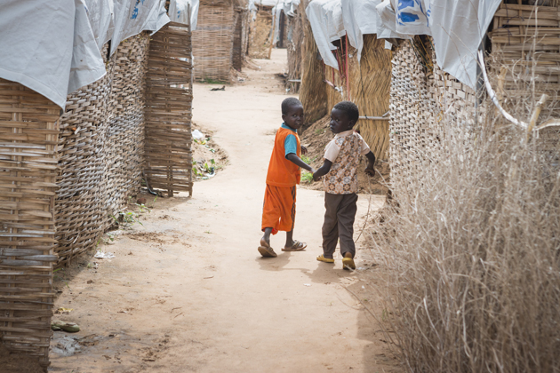 Two young refugee children from South Sudan walk back to their shelter at Al-Nimir camp in Sudan, the day before the High Commissioner's visit in mid-August 2017. ; Since December 2013, over 400,000 South Sudanese have fled to safety in neighbouring Sudan. Al-Nimir camp opened in April 2017 and by mid-August was hosting some 5,800 refugees, nearly all of them women and children from Western Bahr el Ghazal State. As worsening violence continues to force people from their homes in South Sudan, the UN High Commissioner for Refugees Filippo Grandi, visited refugees and the host community in Al-Nimir and called on warring parties, regional states and the international community to urgently establish peace. Conflict and drought have displaced nearly four million South Sudanese both inside the country and beyond its borders. Efforts to restore peace have so far proven unsuccessful.