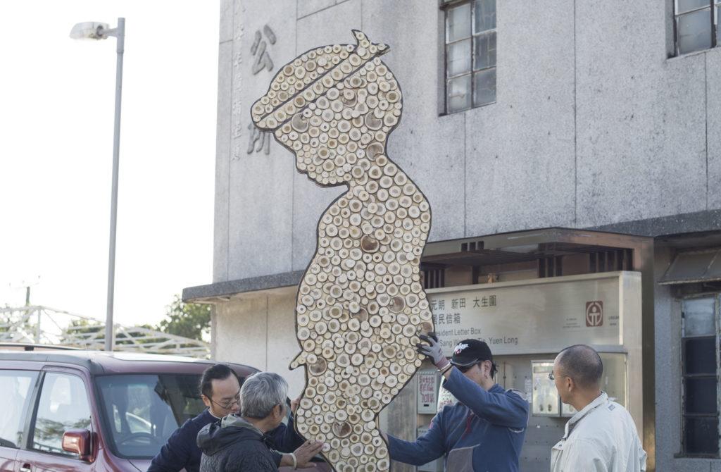 張志平(右二)將完成的作品運進村內進行安裝。