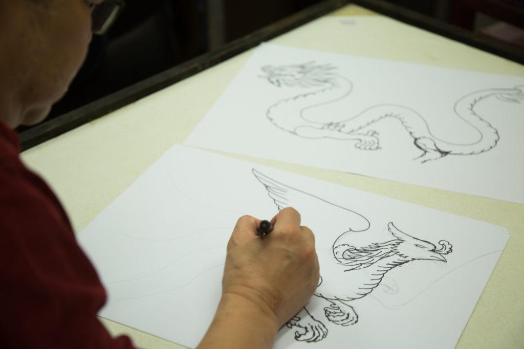 以往十多呎大的龍鳯圖樣他都是白手畫,這樣細張的當然難不倒他。