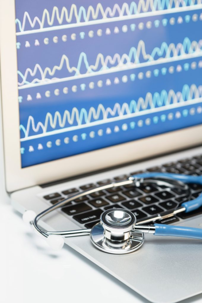 Medical genetics. Acoustic stethoscope on a laptop computer, that displays results of automated DNA sequencing
