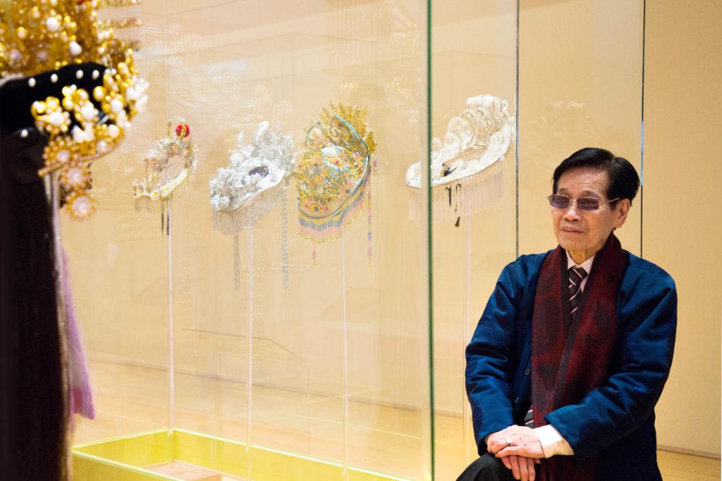 陳國源坐在擺滿自家製盔頭的展示櫃前,滿臉自豪。