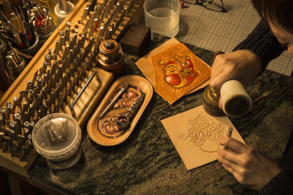 貓頭鷹財神是最受歡近揮春款式,普通桌子無法承受皮雕的力度,所以他們的桌上總會墊着厚重的石塊,皮雕所花的氣力可想而知。
