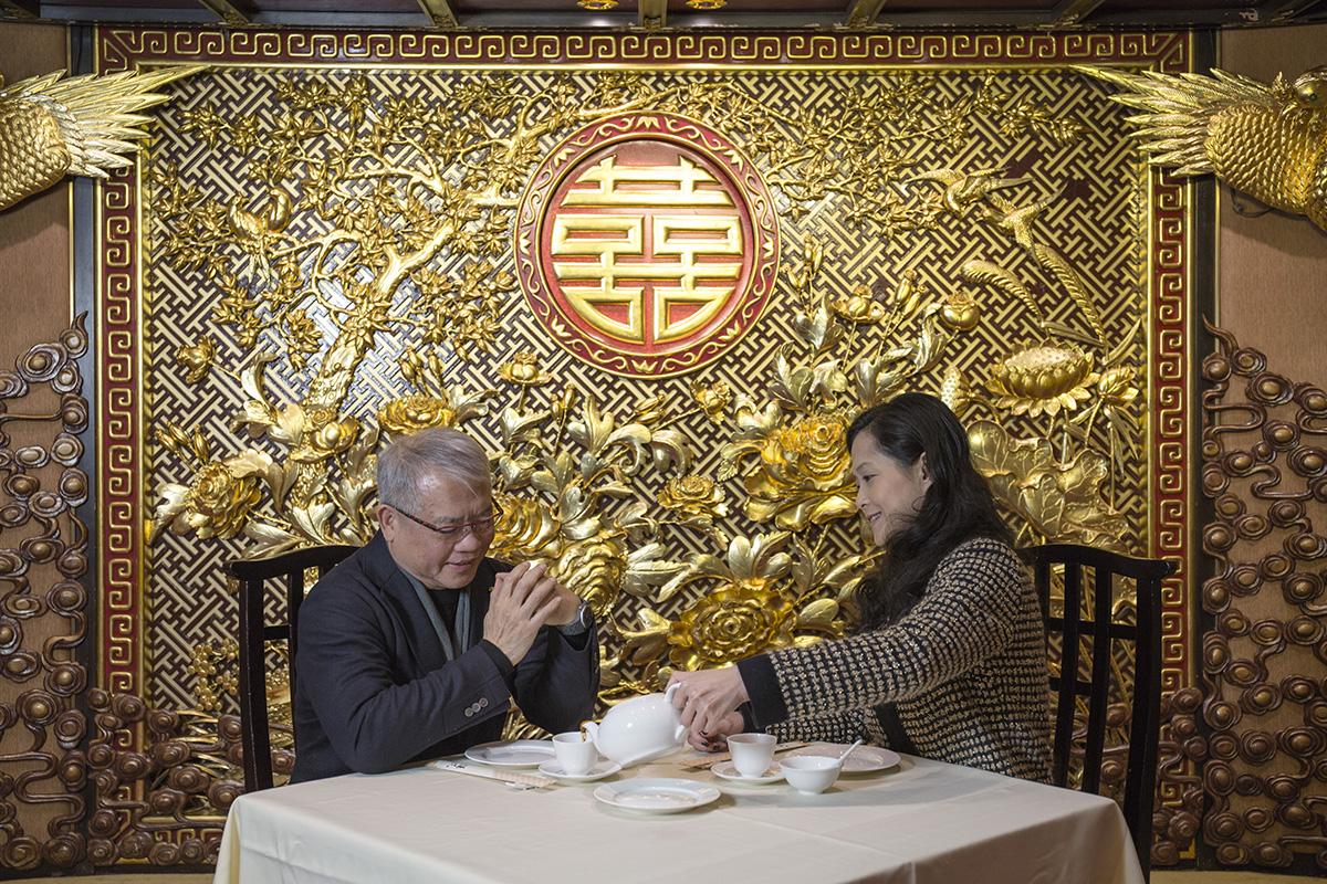 董事及總經理甘琨禮(左)與女兒甘蕎因細談禮堂背景圖案的含意。