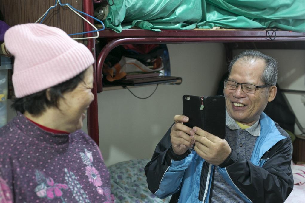 雪英試戴社工送贈的冷帽,(右)廣和馬上執起手機,着太太擰轉頭來拍照。