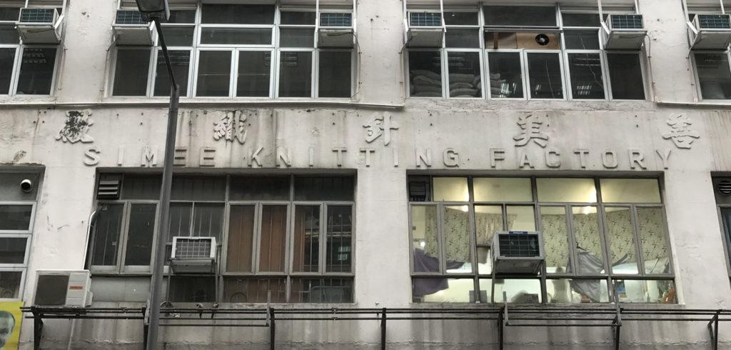 善美針織廠在大廈外牆的水泥字招牌由左至右排列。