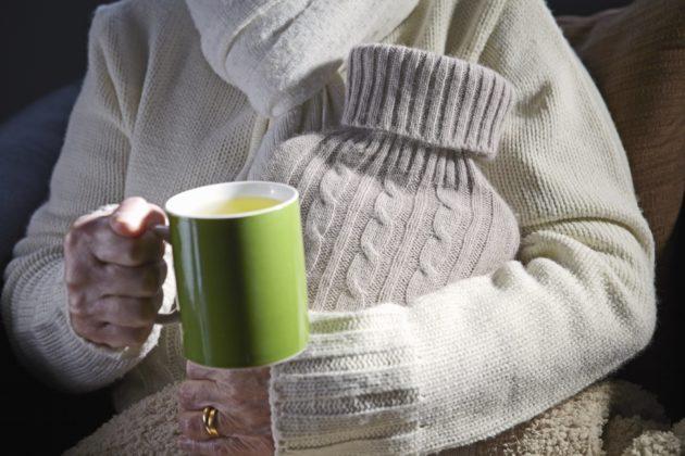 Senior woman holding mug and hot water bottle