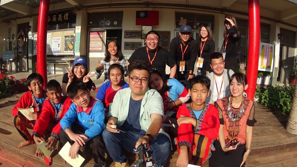 楊文逸(中)與攝影團隊和茶山國小師生自拍留影。學生們為拍攝畢冊,隆重其事地穿起鄒族以白、藍、紅、黑為主調的傳統服飾。