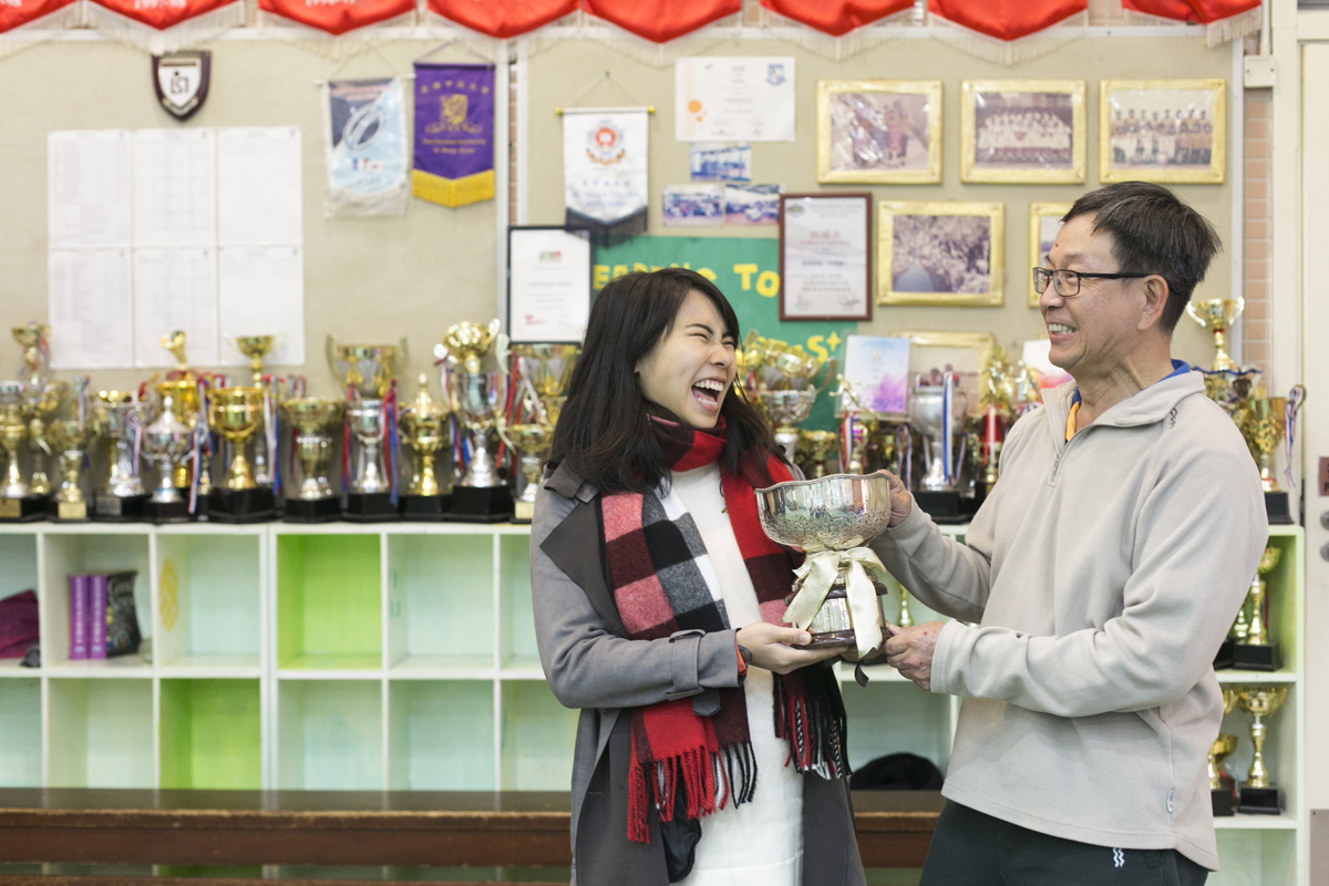 姚潔貞(左)與任教體育三十餘年的吳sir,說起從前訓練,即笑逐顏開。他們背後的獎盃更見證德望運動員的努力不懈。