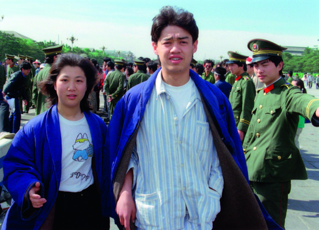 BEIJING, CHINA - MAY 19: Wu'er Kaixi (R), one of the student leaders of the pro-democracy movement walks past a police line along with a fellow student in Tiananmen Square in Beijing 19 May 1989. The 1989 pro-democracy protest was crushed by Chinese troops in June 1989 when army tanks rolled into Tiananmen Square 04 June. (Photo credit should read CATHERINE HENRIETTE/AFP/Getty Images)