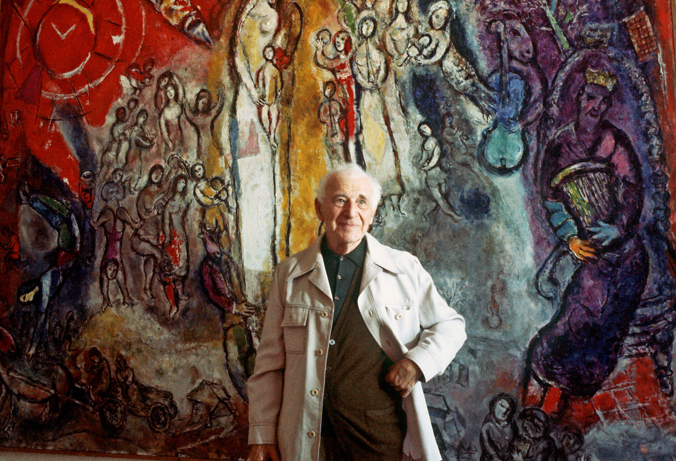 famous painter Marc Chagall, born in Vitebsk, Belarus, poses 02 July 1977 in front of one of his works, inspired with 25 others by Old and New Testament and gathered in Nice for an exhibition in honour of his 90th anniversary. He began to design ballet sets and costumes, illustrated several books, but is best known for his fanciful painting of animals, objects and people of his life, dreams and Russian folklore. / AFP PHOTO / STAFF