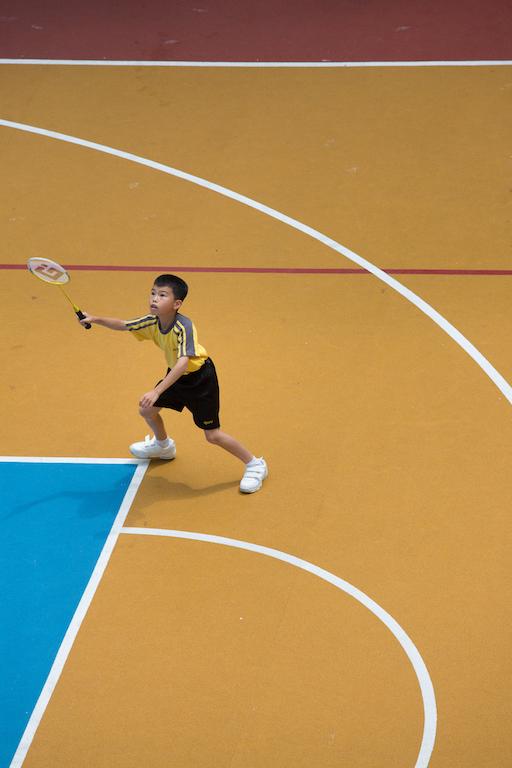 形單隻影的日行在籃球場上打羽毛球