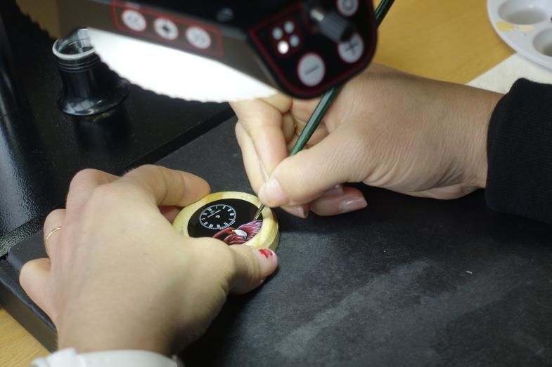 琺瑯工藝師正在繪製去年一枚黑色大明火Petite Heure Minute Pink Flamingo,就地取材以指甲為調色盤。