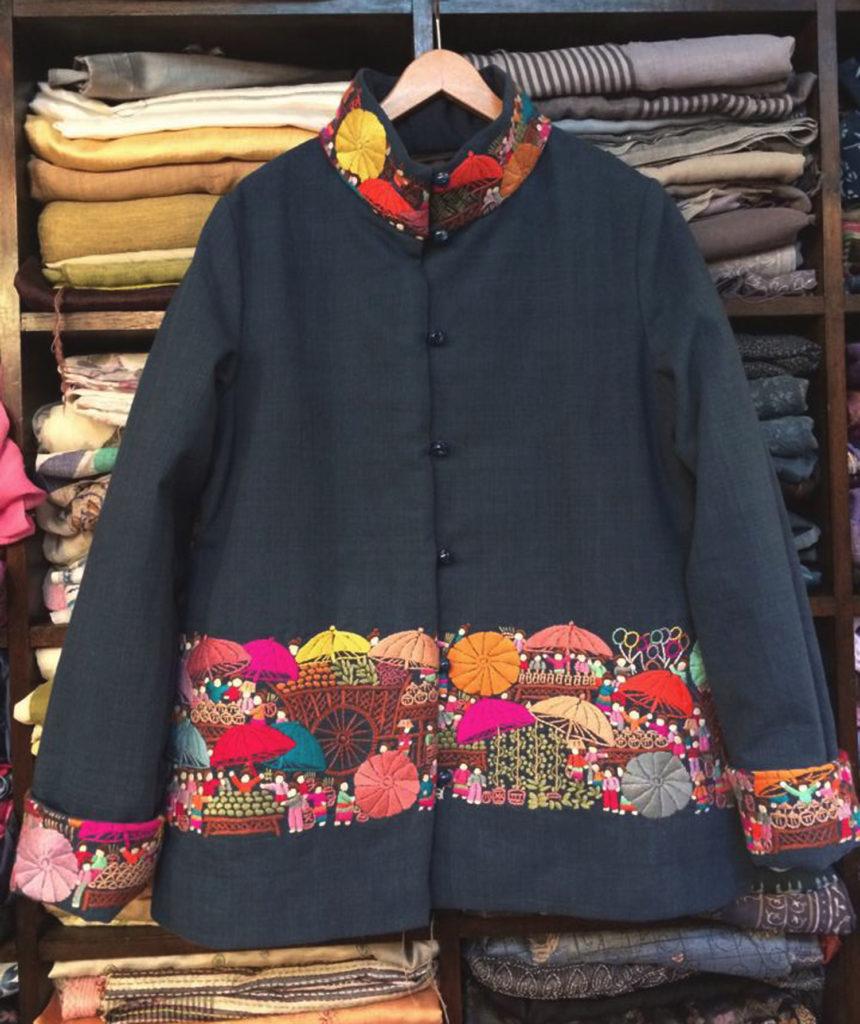 「香港民族服」系列的對襟夾棉外套,繡滿色彩繽紛的雨傘和墟市風貌。