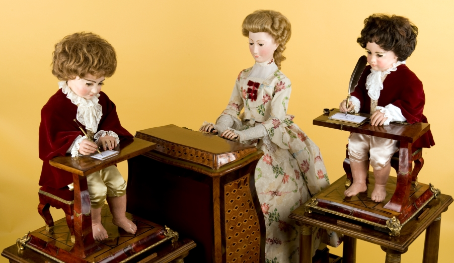 """三個機械人偶至今歷史將近二百五十年; """"The Writer""""(右一)是最早完成的人型玩偶,從背部上鍊後手腕會前後左右移動,以調校書寫位置。"""