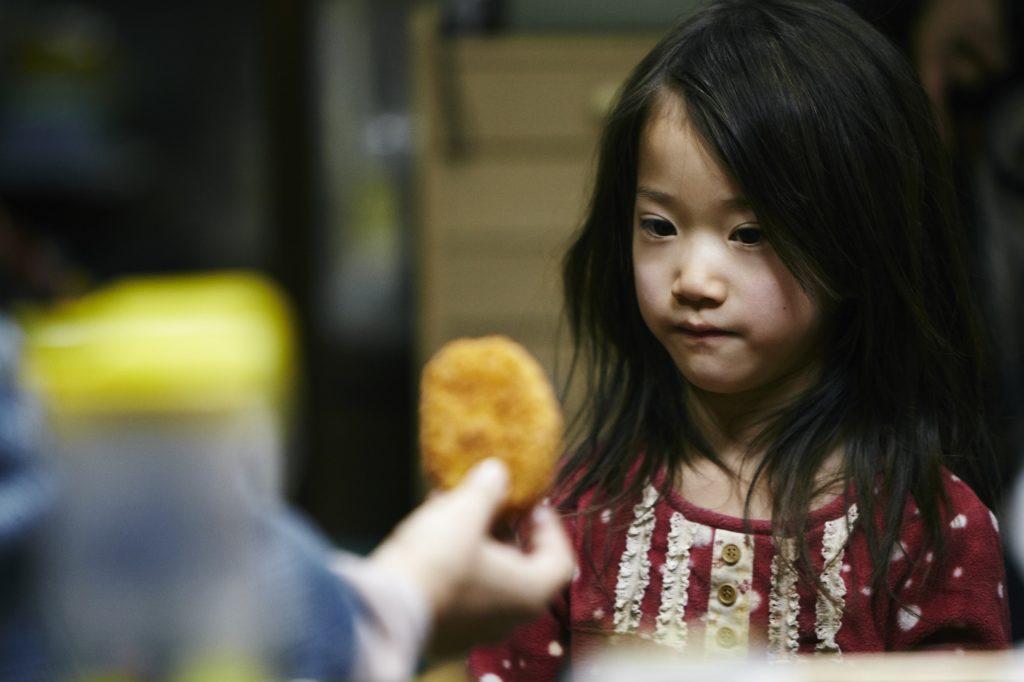 小女孩加入小偷家族,一切由嚴寒的這塊薯餅說起。(《小偷家族》劇照)