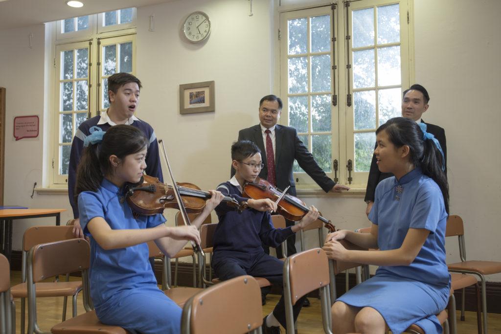 筆者聽着學生譚允靜(左一)與林沛賢(中)一起拉着小提琴和弦時,而蘇穎思(右一)與學生莫家霖(左二)即席演唱,聽出耳油之餘,就連現任中學校長潘紹慈和音樂總監李偉安看到他們的默契也讚賞不已。