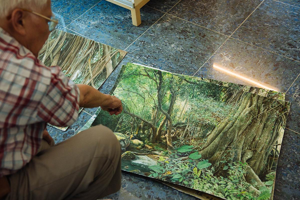江啟明繪畫香港森林,他說,一片綠中其實有很多不同顏色,而畫右邊的粗大樹木與左邊的幼樹及陽光則符合陰陽平衡。
