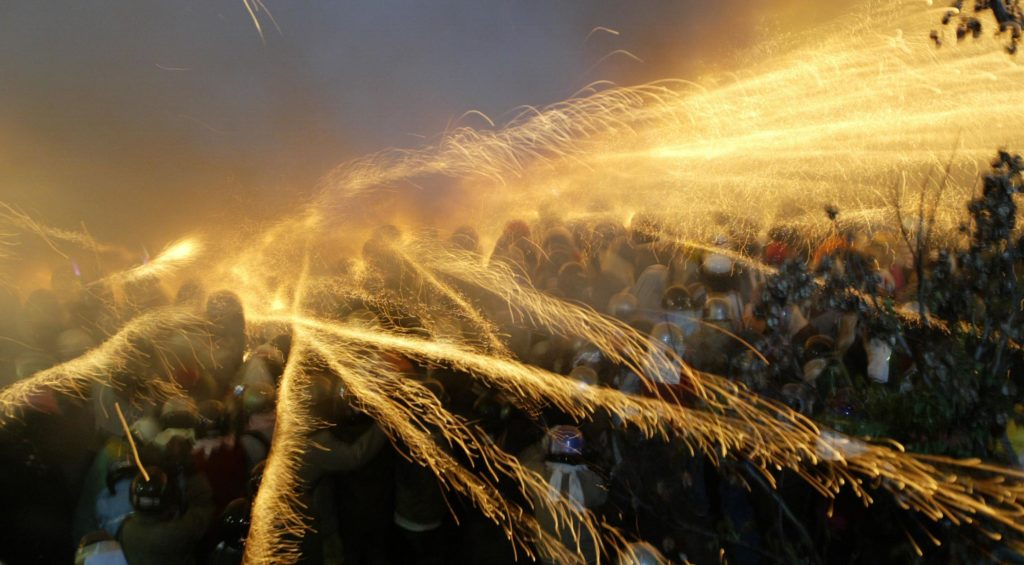 --FILE--Bottle rockets explode and spray fire sparks over visitors during the Yanshui Beehive Rockets Festival in Yanshui District, Tainan city, Taiwan, 27 February 2010.  The Yanshui Beehive Rockets Festival is one of the oldest folk festivals in Taiwan and the third largest in the world. It has been celebrated for over 180 years in the southern district of Yanshui. Its origins date back to 1885, when a cholera epidemic had gripped the district. Due to primitive medical facilities, the disease consumed thousands of victims. Locals lived in a state of fear and prayed to Guan Di, the god of war, to save them. The Beehive Rocket is a multiple launcher of bottle rockets. Thousands of bottle rockets are arranged in rows in an iron-and-wooden framework that looks like a beehive. When the contraption is ignited, the rockets shoot out rapidly in all directions. A deafening, bee-like buzzing sound fills the air. The dazzling explosives whiz and whirl across the sky and into the crowds of dancing people surrounding the beehive. To protect themselves from injuries, locals don heavy clothing, protective gloves and helmets with a full visor. Some also wear a towel around their neck to avoid a stray rocket somehow entering the helmet. Even so, people have been injured in the past. Locals believe in getting bombed by as many firecrackers as possible for good luck in the coming year. Visitors from all over the nation and even foreign tourists crowd at the Yanshui Wu temple well ahead of time, to find a good spot before the Beehive Festival starts. It begins at 6:00 pm and goes on until 5:00 am the following morning.