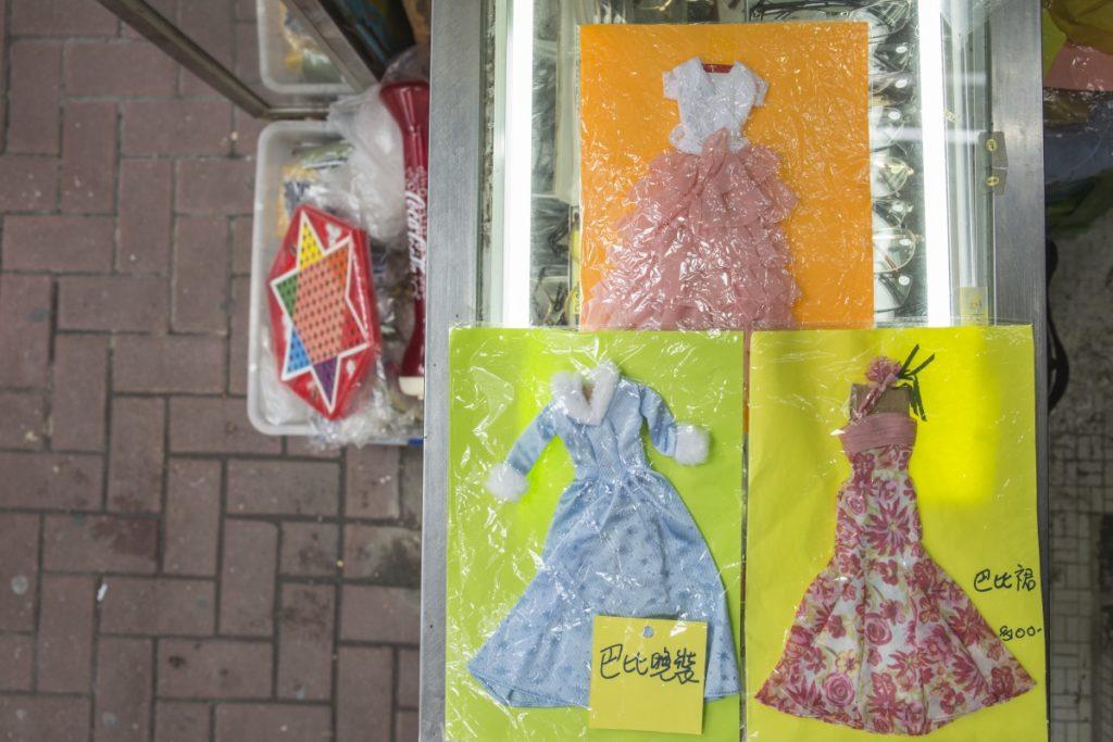 朋友把心愛的芭比晚裝放在店內寄賣,周姐細心襯上色紙,用透明袋包裝,以免被雨水淋濕。