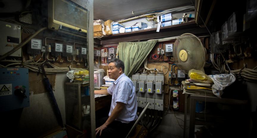 王沛龍每天就坐在由電錶房改裝而成的樓梯舖中。
