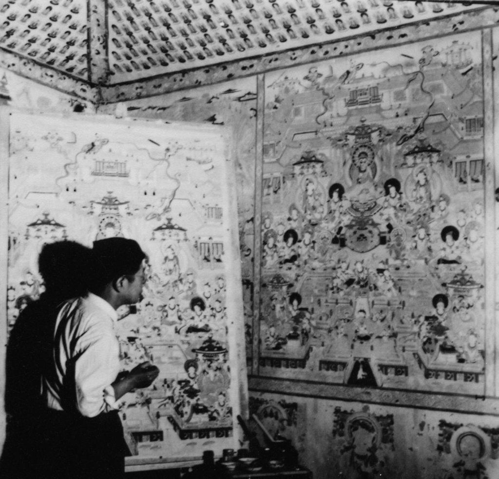 敦煌研究院首任院長常書鴻,1945年在莫高窟洞內臨摹壁畫的情況。